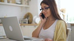 小姐与膝上型计算机一起使用,谈话在电话在家庭环境的桌上 影视素材