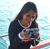 小姐喜欢看在她的佩戴水肺的潜水一台水下的照相机的照片  图库摄影