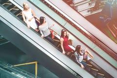 小姐在自动扶梯乘坐 他们逐个站立 每一个有购物袋 他们是 免版税库存图片