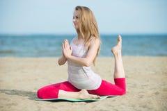 小姐实践的瑜伽 在海洋沿海附近的锻炼 图库摄影