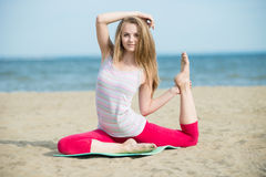 小姐实践的瑜伽 在海洋沿海附近的锻炼 库存图片