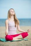 小姐实践的瑜伽 在海洋沿海附近的锻炼 免版税图库摄影