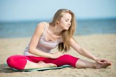小姐实践的瑜伽 在海洋海附近的锻炼 库存图片