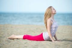 小姐实践的瑜伽 在海洋海附近的锻炼 免版税库存图片