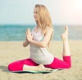 小姐实践的瑜伽 在海洋海附近的锻炼 免版税库存照片