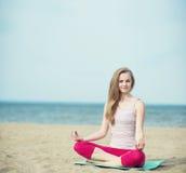 小姐实践的瑜伽 在海洋海附近的锻炼 免版税图库摄影