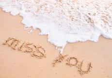 小姐您,在沙子的词,接触由移动的波浪 免版税库存图片