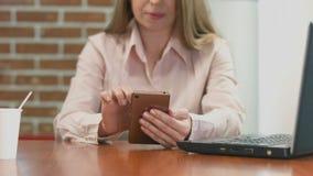 小姐浏览互联网,读新闻在咖啡馆的智能手机 股票录像