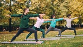 小姐瑜伽学生在然后搬入三角位置的战士姿势站立在室外类期间在公园 股票视频