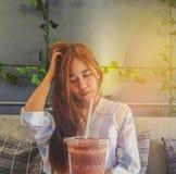 小姐,十几岁的女孩饮料抽象软的焦点在塑料玻璃的凉快的咖啡在有射线光的, s屋子里 库存照片