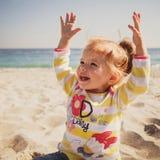 小婴孩、小女孩蓝色牛仔裤的,桃红色坐和使用在沙子的鞋子和五颜六色的套头衫在海滩 免版税库存照片