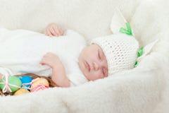 小婴孩兔宝宝盖帽穿戴的复活节彩蛋 库存图片