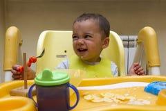 小婴孩吃与匙子汤盘 他坐儿童` s椅子,投入食物 免版税库存图片