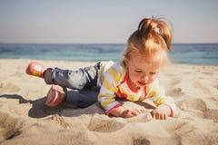 小婴孩,蓝色牛仔裤的小女孩,桃红色鞋子和五颜六色 库存图片