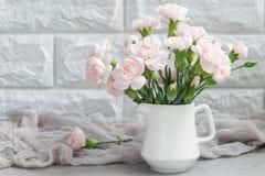 小嫩桃红色康乃馨在灰色混凝土的花瓶开花与拷贝空间,水平 免版税库存照片