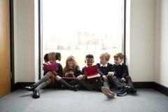 小学孩子连续坐在一个窗口前面的地板在学校走廊使用片剂计算机,正面图 免版税库存照片