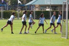 小学生给他们的肌肉加热在期间户外运动c 库存图片