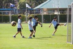 小学生给他们的肌肉加热在期间户外运动c 免版税库存照片