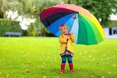 小学龄前儿童女孩画象有五颜六色的伞的 库存图片