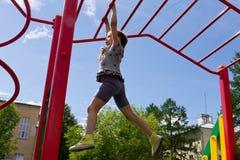 小学龄前沿猴子栏杆的女孩垂悬的步行 图库摄影