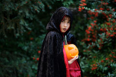 小学年龄的男孩在一个黑红色斗篷的刻画邪恶的巫师 免版税库存照片