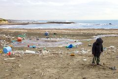 小孩不关心对被污染的海滩的土和危险 库存图片