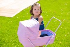 小孩使用与在绿色草皮的婴孩推车的孩子女孩 免版税图库摄影