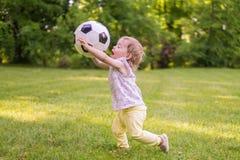 小孩使用与橄榄球球在公园 免版税库存图片