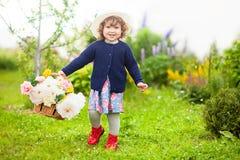 小孩卷毛有篮子的头发女孩有很多花:牡丹和ro 免版税库存图片