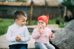 小孩吃冰淇淋的兄弟和姐妹户外 图库摄影