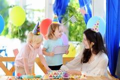 小孩和他们的母亲庆祝与五颜六色的装饰的与五颜六色的装饰的生日聚会和蛋糕并且结块 库存照片