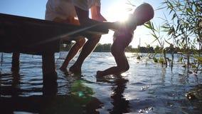 小孩和他的爸爸摇摆的脚在水中在晴天 坐在木跳船边缘的年轻爸爸在湖 股票视频
