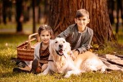 小孩和狗坐野餐毯子 免版税库存图片