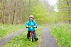 小孩在一辆自行车的男孩骑马在森林里 免版税库存图片