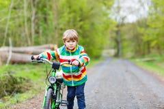 小孩在一辆自行车的男孩骑马在森林里 免版税图库摄影