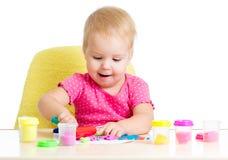 小孩在使用与五颜六色的黏土的表 免版税库存图片