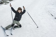小孩在冬天雪山的滑雪跌倒 库存图片