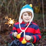 小孩在冬天给拿着灼烧的闪烁发光物穿衣 免版税库存图片