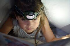小孩在床上读了书在盖子下在晚上 库存照片