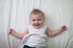小孩在床,第一颗牙上的笑婴孩 免版税库存照片