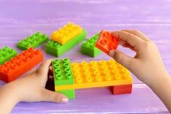 小孩在他的手上拿着设计师块,并且供玩具住宿 在淡紫色背景的色的塑料建设者 库存照片