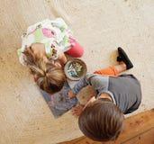 小孩坐与颜色的地板图画用粉笔写 免版税图库摄影