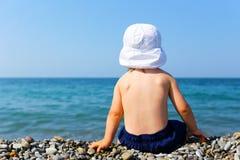 小孩坐石海滩 免版税库存图片