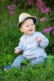 小孩坐草在草甸 backgrou的一个婴孩 库存图片