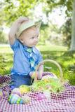 小孩外部举行的复活节彩蛋打翻他的帽子 免版税库存照片