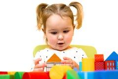 小孩女孩使用与在白色背景的五颜六色的木块 小孩修建房子在块外面 免版税库存图片