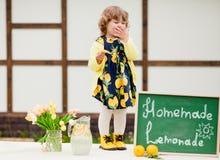 小孩女孩卖lemonde并且吃柠檬 库存图片