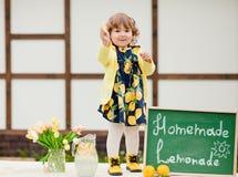 小孩女孩卖lemonde并且吃柠檬 库存照片