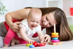 小孩女孩和她的妈妈在家使用与颜色玩具 免版税库存图片