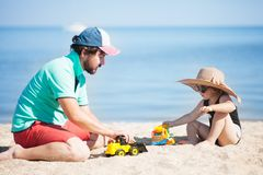 小孩女孩和她的父亲海滩的 库存照片